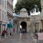 Brama Morska stanowiąca przejście przez mury obronne zawiera fragment dawnego łuku rzymskiego