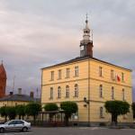 Jutrosin – klasycystyczny ratusz z połowy XIX w. W tle kościół św. Elżbiety