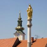 Na placu przed katedrą stoi słup ze złotą figurą Matki Boskiej