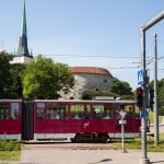 Na pierwszym palnie drogowskaz droga rowerowa skręca w prawo, na drugim wysłużały tramwaj, a w tle mury miejskie (ich łączna długość wynosi ponad półtora kilometra