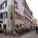 """Ruch rowerowy w ścisłym centrum jest zakazany – rowery stoją zaparkowane przed apteką """"Mohren Apotheke"""" W staroniemieckim """"Mohr"""" odnosiło się do ludzi o ciemnym zabarwieniu skóry. Tu na rogu apteki widzimy czarnoskórego księcia z tarczą i złotą koroną"""