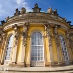 Poczdam – Pałac Sanssouci – Elewacja ogrodowa: brązowy napis Sans. Souci oraz figury bachantów i bachantek – w mitologii greckiej towarzysze i czcicielki Dionizosa