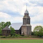 Nowe Dwory. Drewniana dzwonnica konstrukcji słupowej z 1826, Kościół i cmentarz otacza mur z kamienia.